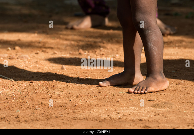 Indian babies bare legs and feet casting a shadow on the earth in a rural indian village. Andhra Pradesh, India - Stock Image
