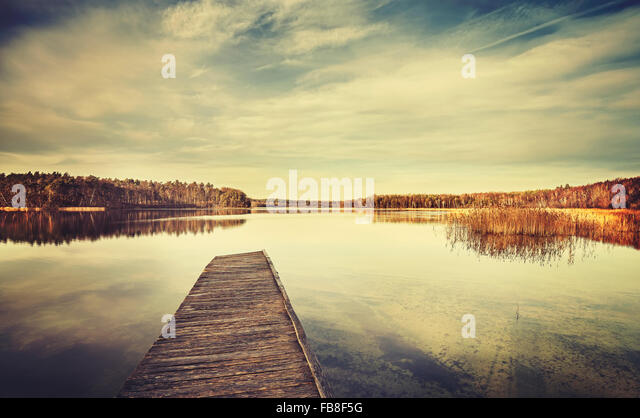 Vintage stylized picture of a lake and wooden pier. - Stock-Bilder