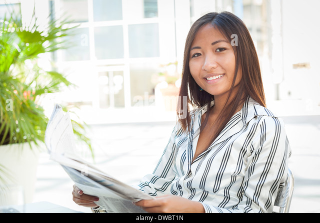 Portrait of a beautiful asian girl reading newspaper - Stock Image