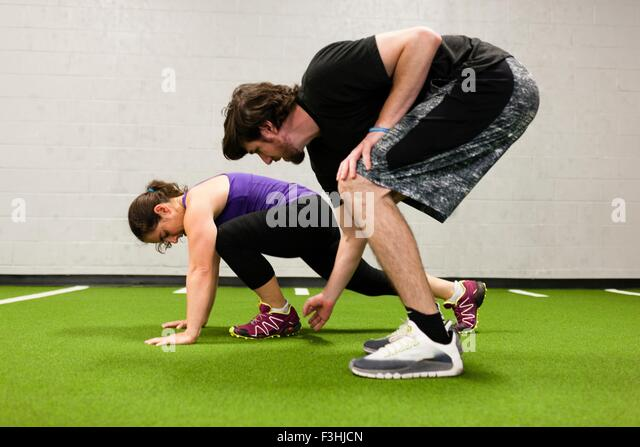 Personal trainer working with mid adult woman in gym - Stock Image