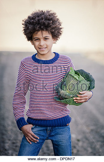 Portrait of boy in field holding cabbage - Stock Image