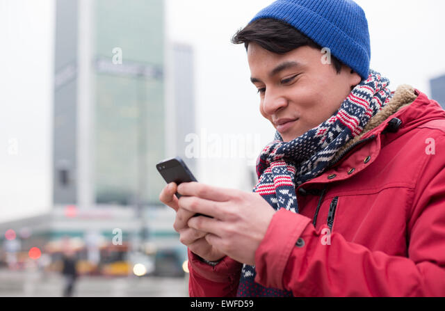 Smiling man using cell phone in city during winter - Stock Image