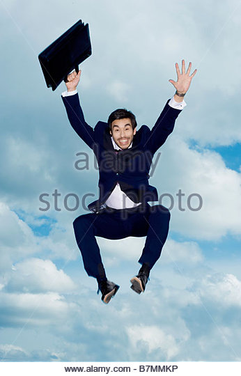 A businessman with briefcase, leaping in the air - Stock Image