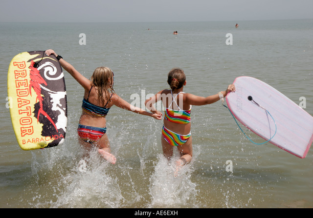 Toledo Ohio Oregon Maumee Bay State Park Lake Erie girls boards splash water - Stock Image