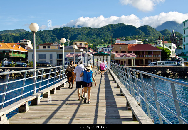 Cruise pier leading toward Roseau, Dominica, with cruise passengers walking on pier - Stock Image