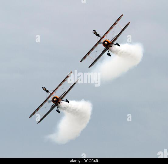 Eastbourne, East Sussex, UK. 16 August 2013. Breitling Wingwalkers perform breathtaking acrobatics on 1940s Boeing - Stock Image