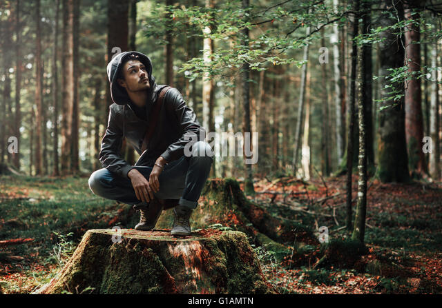 Young handsome man exploring the forest and looking around, nature and freedom concept - Stock Image
