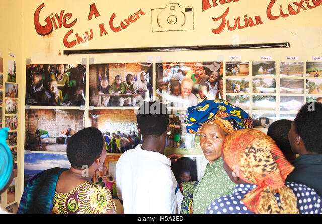 The school opens up during the Exhibition in rural Uganda where the local community attends to view photos - Stock Image