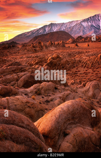 Rocks and boulders in California's Alabama HIlls at sunrise with the Sierra Nevada range as backdrop - Stock Image