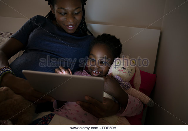 Mother and daughter using digital tablet at bedtime - Stock Image