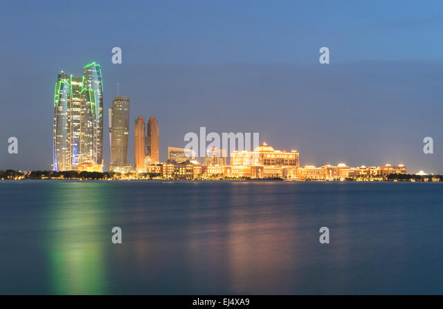 Evening skyline view of Abu Dhabi with Emirates Palace Hotel  in United Arab Emirates - Stock Image
