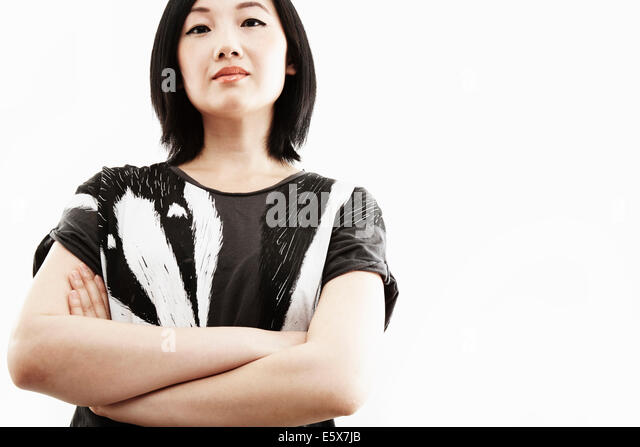 Studio portrait of young woman with arms folded - Stock Image