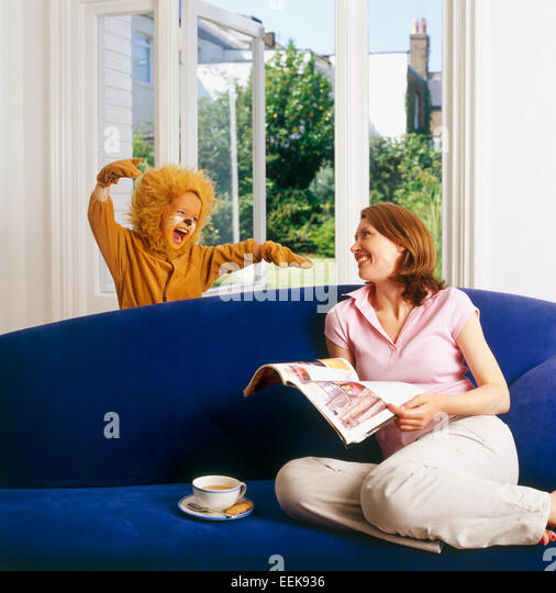 Mum at home sitting relaxing, reading a newspaper, her child dressed as lion surprises her from behind the sofa, - Stock Image