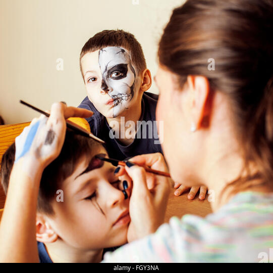 little cute child making facepaint on birthday party, zombie Apocalypse facepainting, halloween preparing - Stock-Bilder
