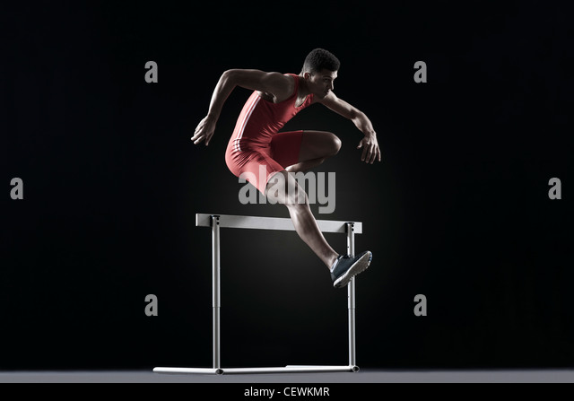 Male athlete cearling hurdle - Stock Image