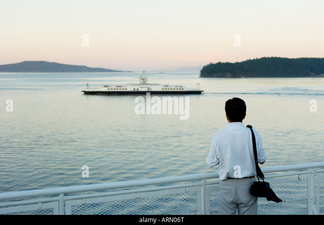 View from deck of BC Ferry, passenger watches smaller Gulf Island Ferry near Sidney, Vancouver Island, Britsh Columbia, - Stock Image