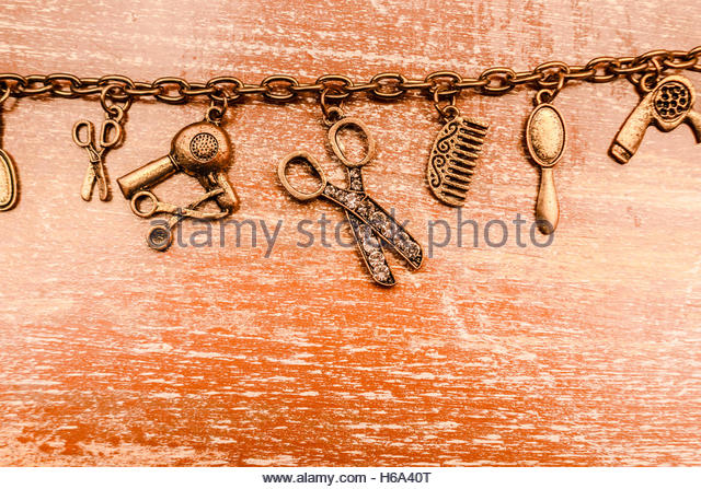 Beautician background on expensive hairdresser tools on link chain with wooden background. Salon hair cut tools - Stock Image