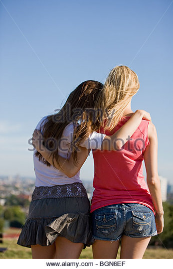 Two young women looking across the city, rear view - Stock-Bilder