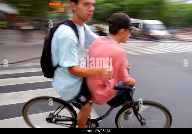 Argentina Buenos Aires Avenida Rivadavia street scene intersection bicycle cyclist motion traffic Hispanic man teen - Stock Image