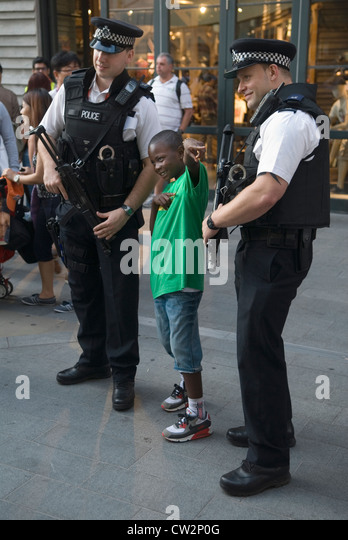 London Olympics young boy poses for photograph with two British armed policeman on duty at th e Olympics HOMER SYKES - Stock Image