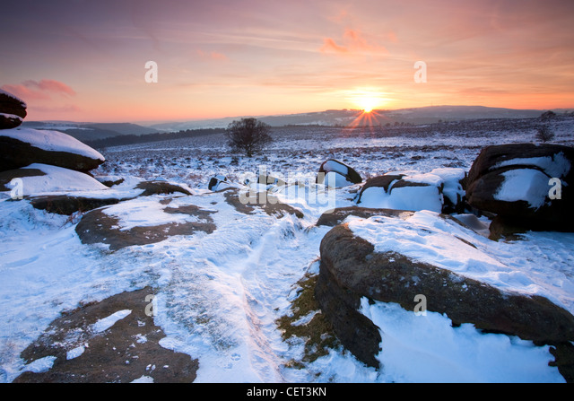 Sunset viewed from snow covered Over Owler Tor in the Peak District National Park. - Stock Image