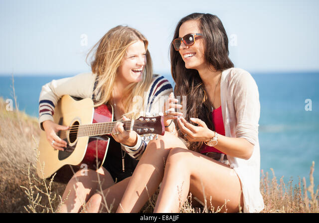 Two young women with acoustic guitar at coast, Malibu, California, USA - Stock Image