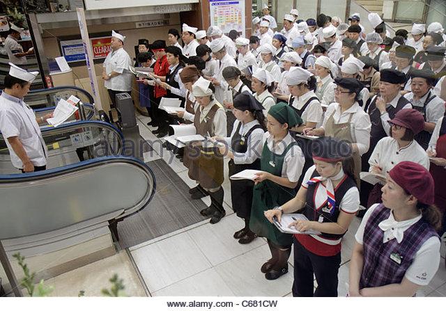 Tokyo Japan Shinjuku Shinjuku Station restaurant employees servers cooks chefs uniforms morning meeting before work - Stock Image