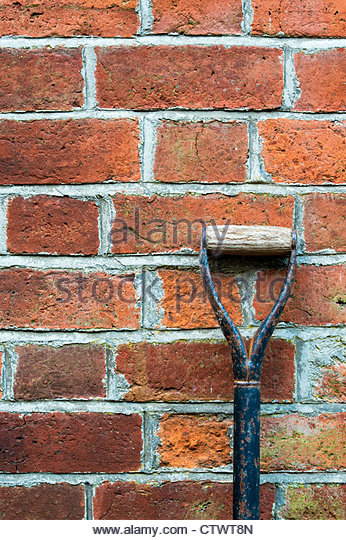 Garden spade handle against a red brick wall. UK - Stock Image