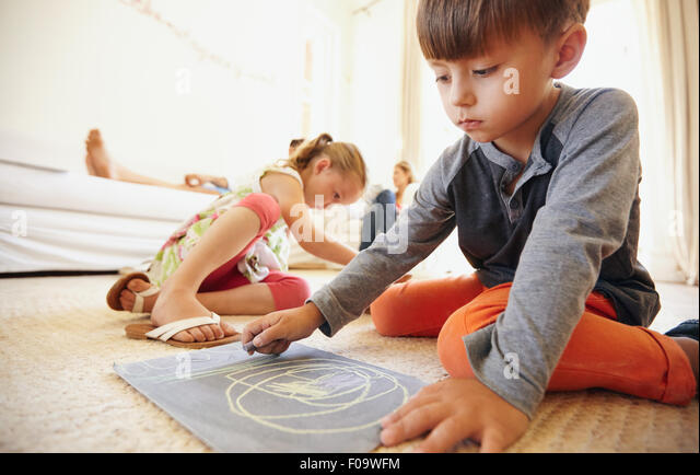 Little boy drawing and coloring while sitting on floor in living room. Children on floor painting with parents sitting - Stock Image
