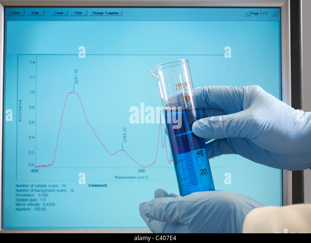 Hands holding sample in front of monitor - Stock Image