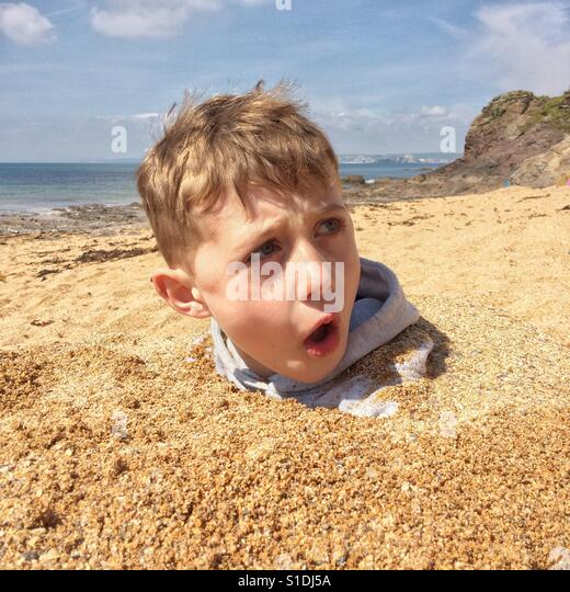 Seven year old boy playing in the sand at Hope Cove, Devon,England - Stock-Bilder