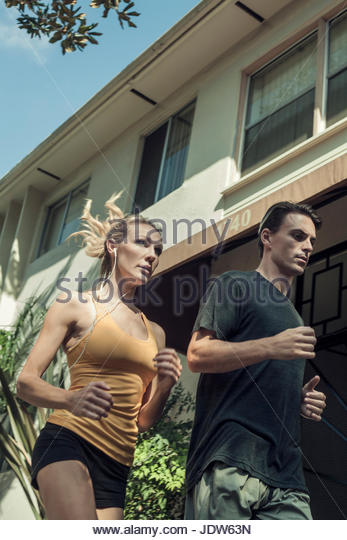 Young couple jogging in street, low angle view - Stock-Bilder