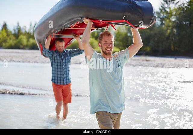 Two men carrying dinghy above their heads through shallow water - Stock Image