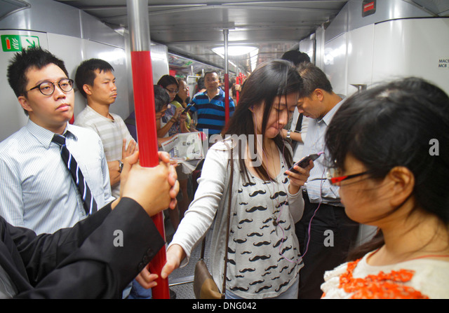 Hong Kong China Island MTR North Point Subway Station public transportation train cabin passengers riders standing - Stock Image