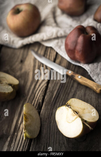 Red apples and apple halves on a wooden table vertical - Stock Image