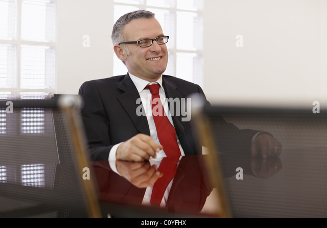 Portrait of caucasian mid adult business man talking to colleagues in meeting room. Horizontal shape, side view, - Stock Image