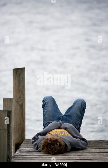 Boy relaxing on a pier in Marlborough Sound New Zealand - Stock-Bilder