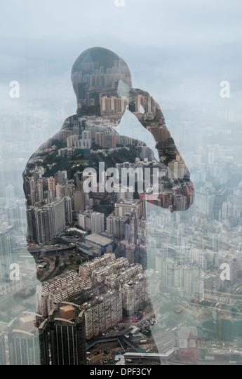 Businessman using smartphone and Hong Kong cityscape, composite image - Stock Image