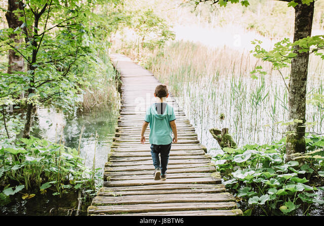 Boy walking on a wooden path throught nature - Stock Image