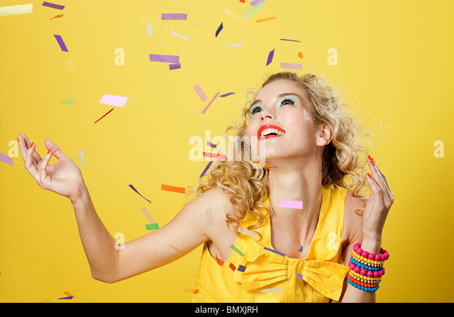 Young blonde woman with colourful confetti - Stock Image