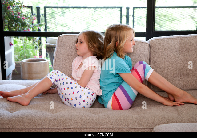 two girls sitting on the couch back to back - Stock Image