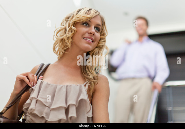 Smiling woman carrying purse - Stock Image