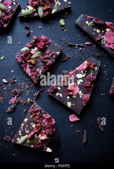 Handmade chocolate with berries, jpistachios and edible gold - Stock Image