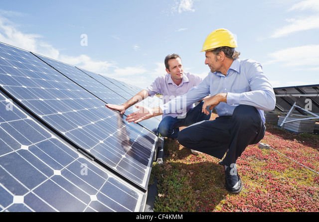 Germany, Munich, Man discussing with engineer in solar plant - Stock Image
