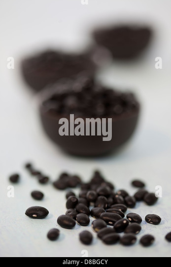 A small pile of black beans in front of three small bowls of black beans on a white wood surface. - Stock Image