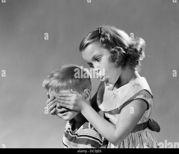 1950s 1960s GUESS WHO GIRL HOLDS HER HANDS OVER BOYS EYES BLIND GAME TEASING PLAYING BOY GIRLS - Stock Image