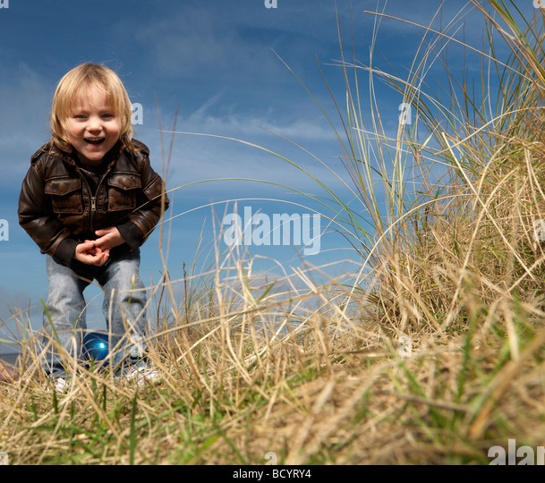 boy at beach playing with ball - Stock Image