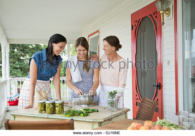 Female family members preparing to can vegetables - Stock Image