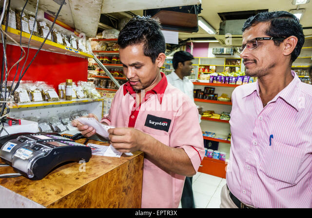 India Asian Mumbai Churchgate Suryodaya grocery store supermarket man employee credit card scanner using uniform - Stock Image