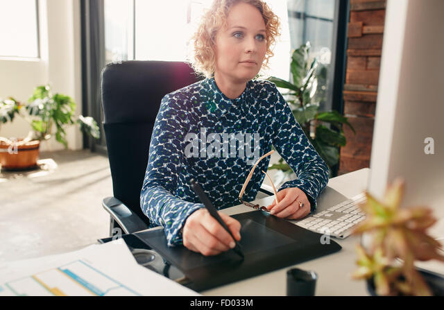 Young female editor using graphics tablet to do work at her desk in the office. Professional graphic designer at - Stock Image